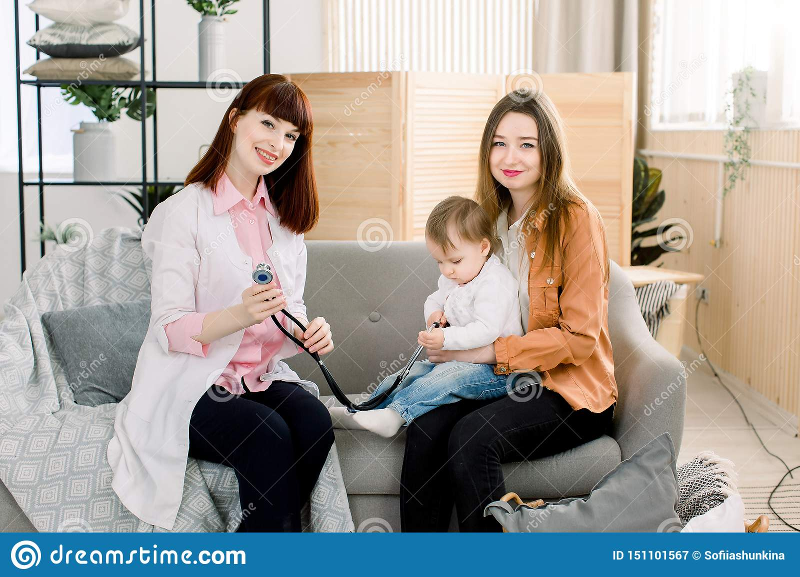 Medicine, healthcare, pediatry and people concept - woman with baby and young woman doctor at clinic or at home