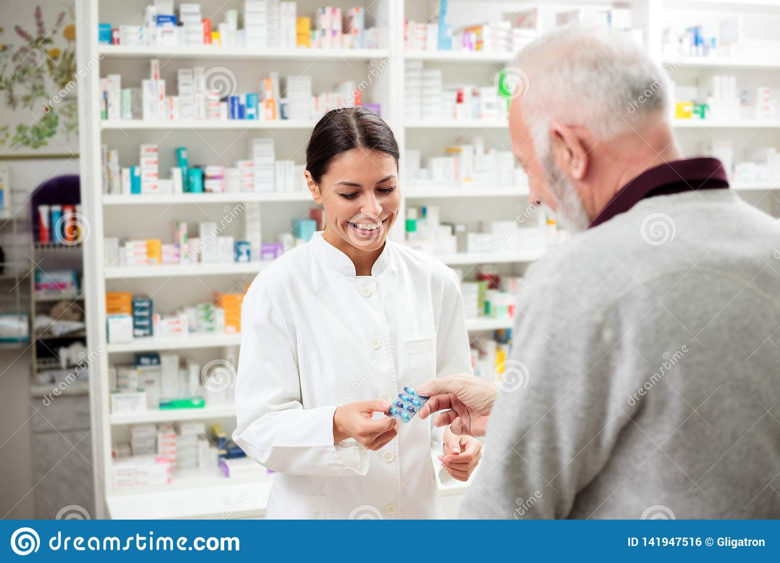 Smiling young female pharmacist giving prescription medication pills to senior male patient