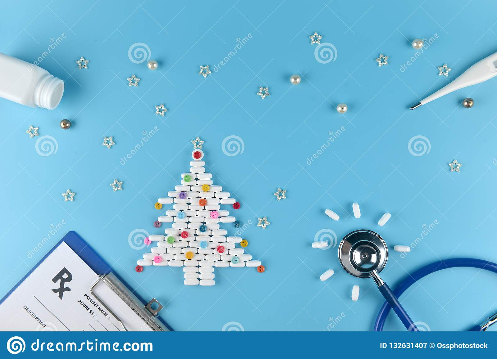 medicine pills shape of christmas tree and others equipment of doctor on blue background concept christmas and new year