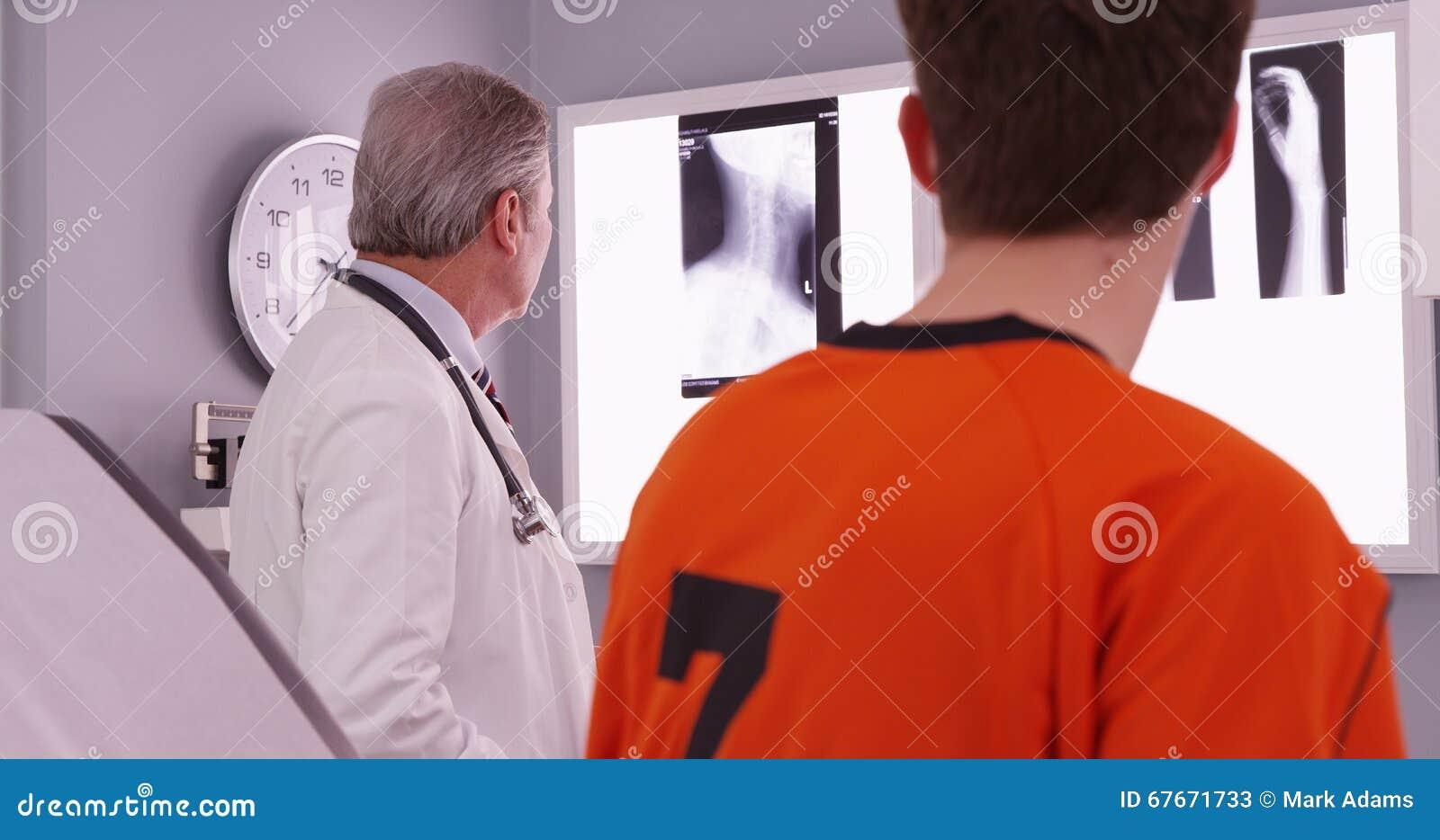 Medicinsk doktor som granskar sportidrottsman nen röntgenstrålar för skada för hals