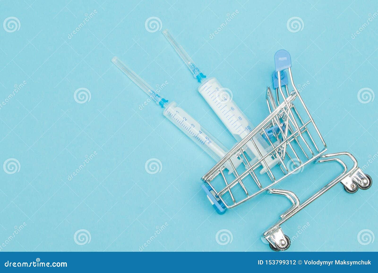 Medicinsk injektion, i att shoppa sp?rvagnen p? bl? bakgrund Id?rik id? f?r h?lsov?rdkostnad, apotek, sjukf?rs?kring och