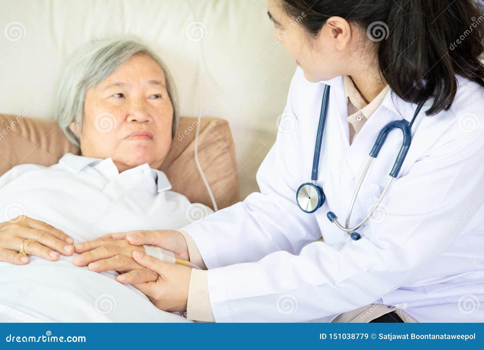 Medicinsk kvinnlig doktor eller sjuksköterska som rymmer höga tålmodiga händer och tröstar henne på sjukhussäng eller hemmet, han