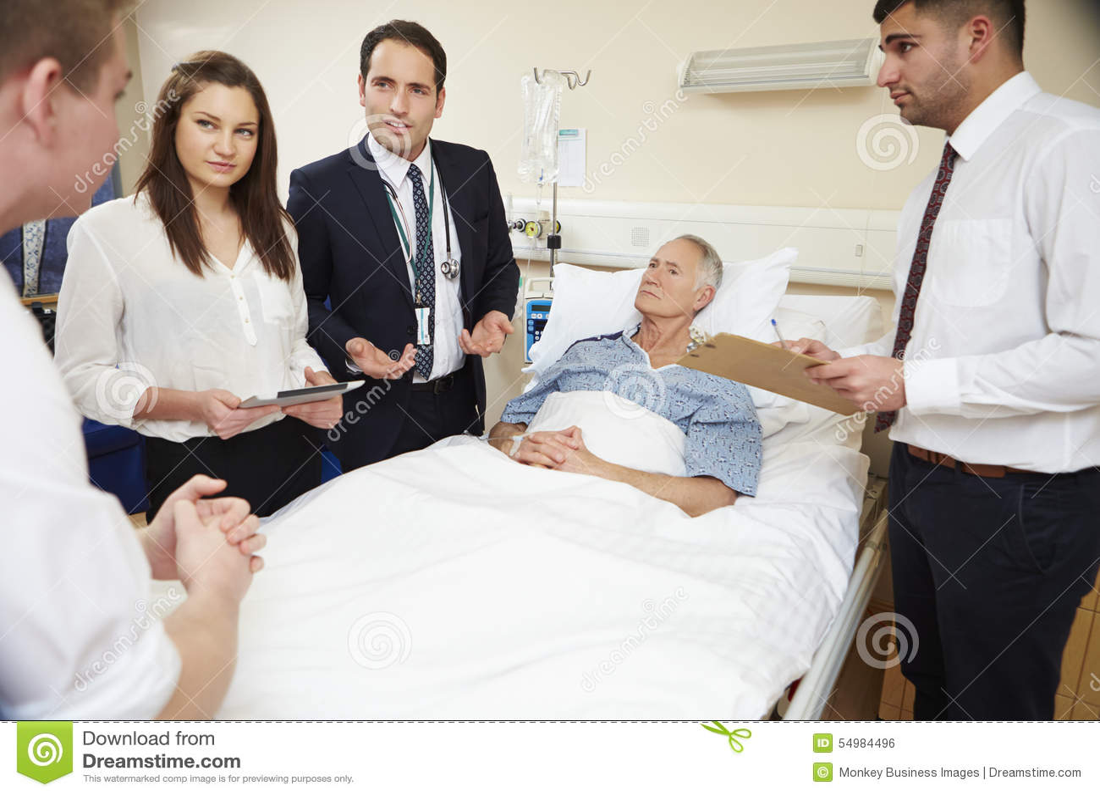 Medicinsk personal på rundor som står vid manlig patients säng
