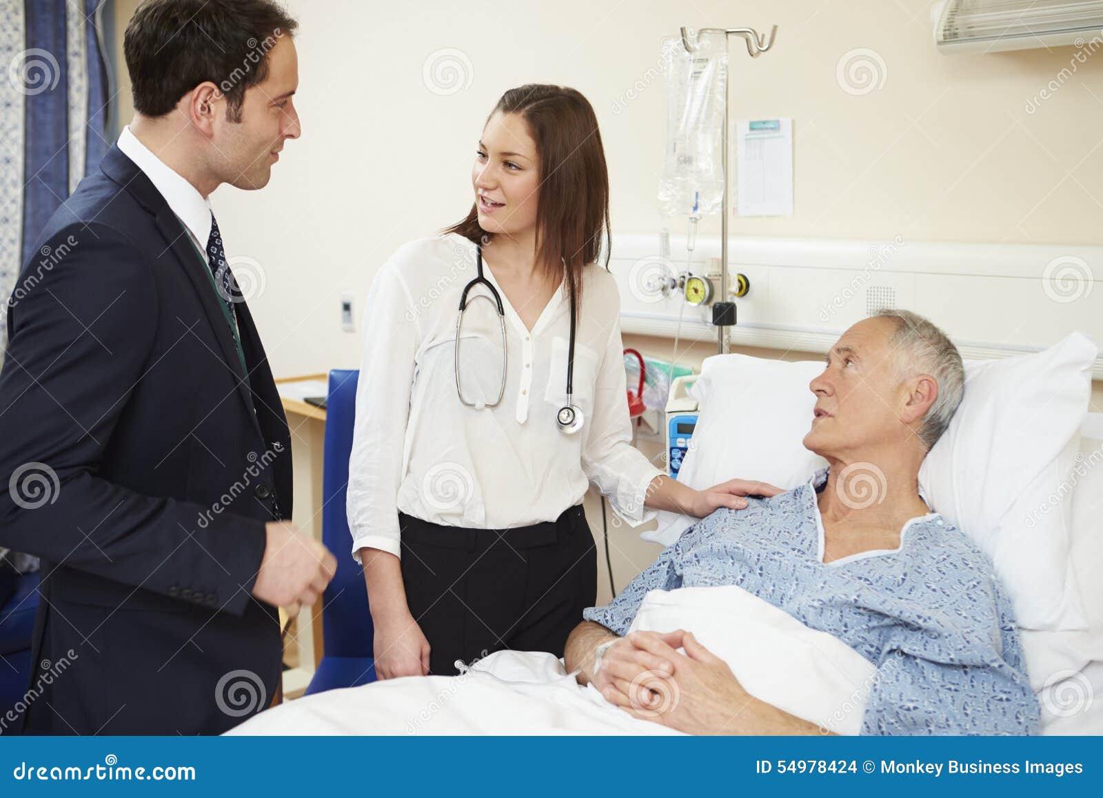 Medicinsk personal på rundor som undersöker den höga manliga patienten