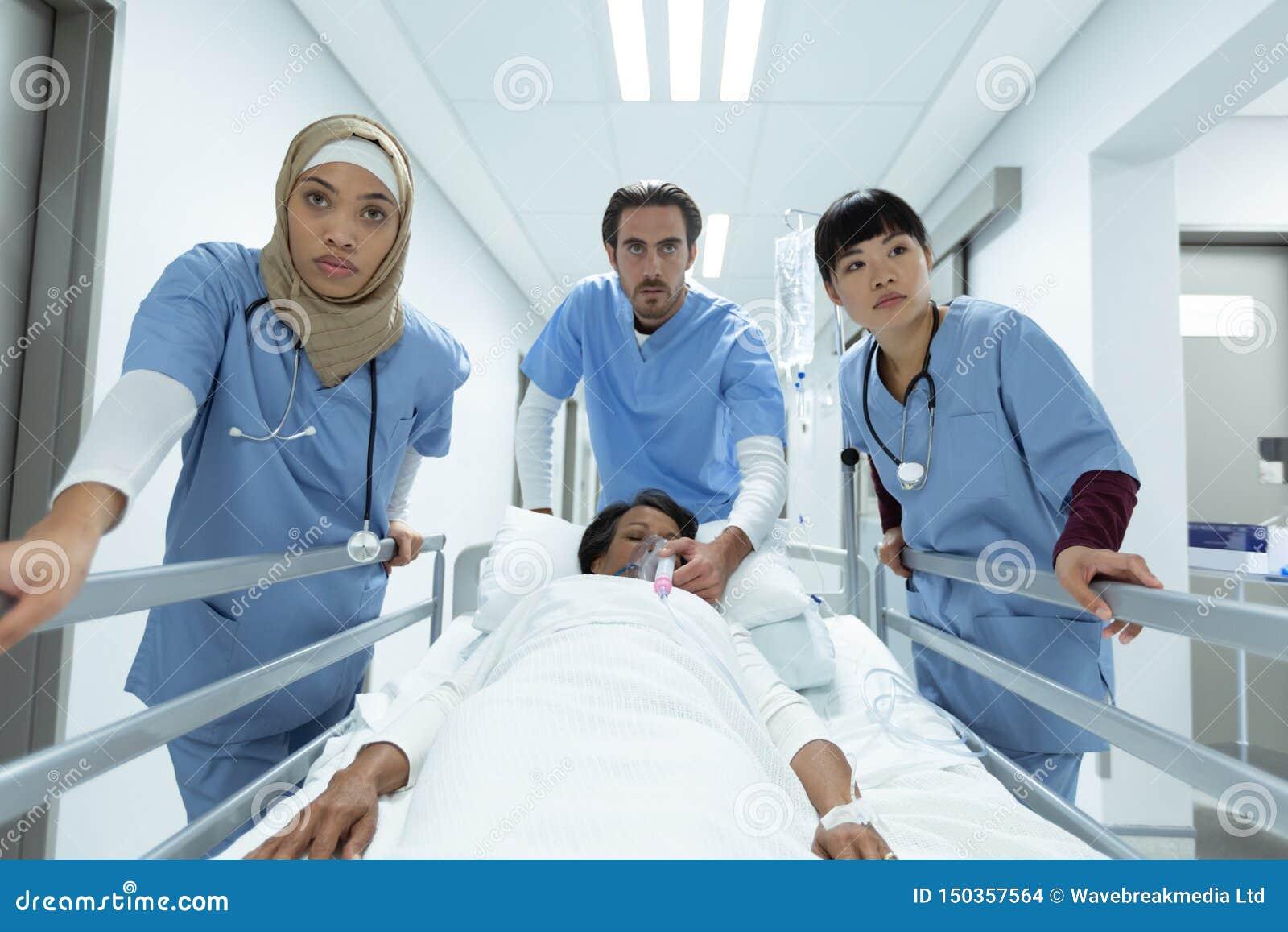 Medicinskt lag som skjuter nöd- bårsäng i korridor