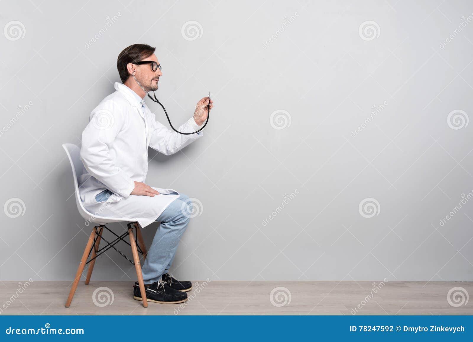 Medico bello che diagnostica il paziente
