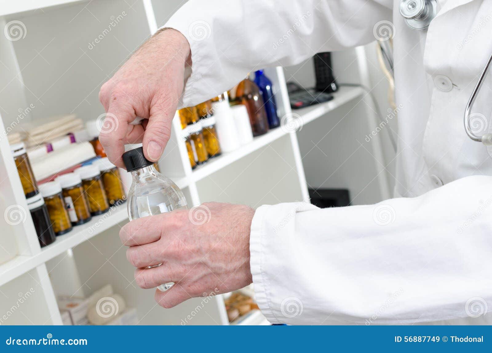Medico che apre una bottiglia del disinfettante