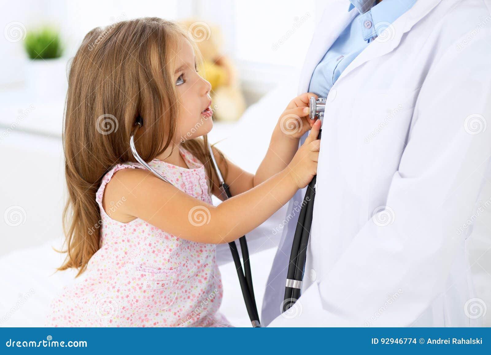 Medico che esamina una bambina secondo lo stetoscopio