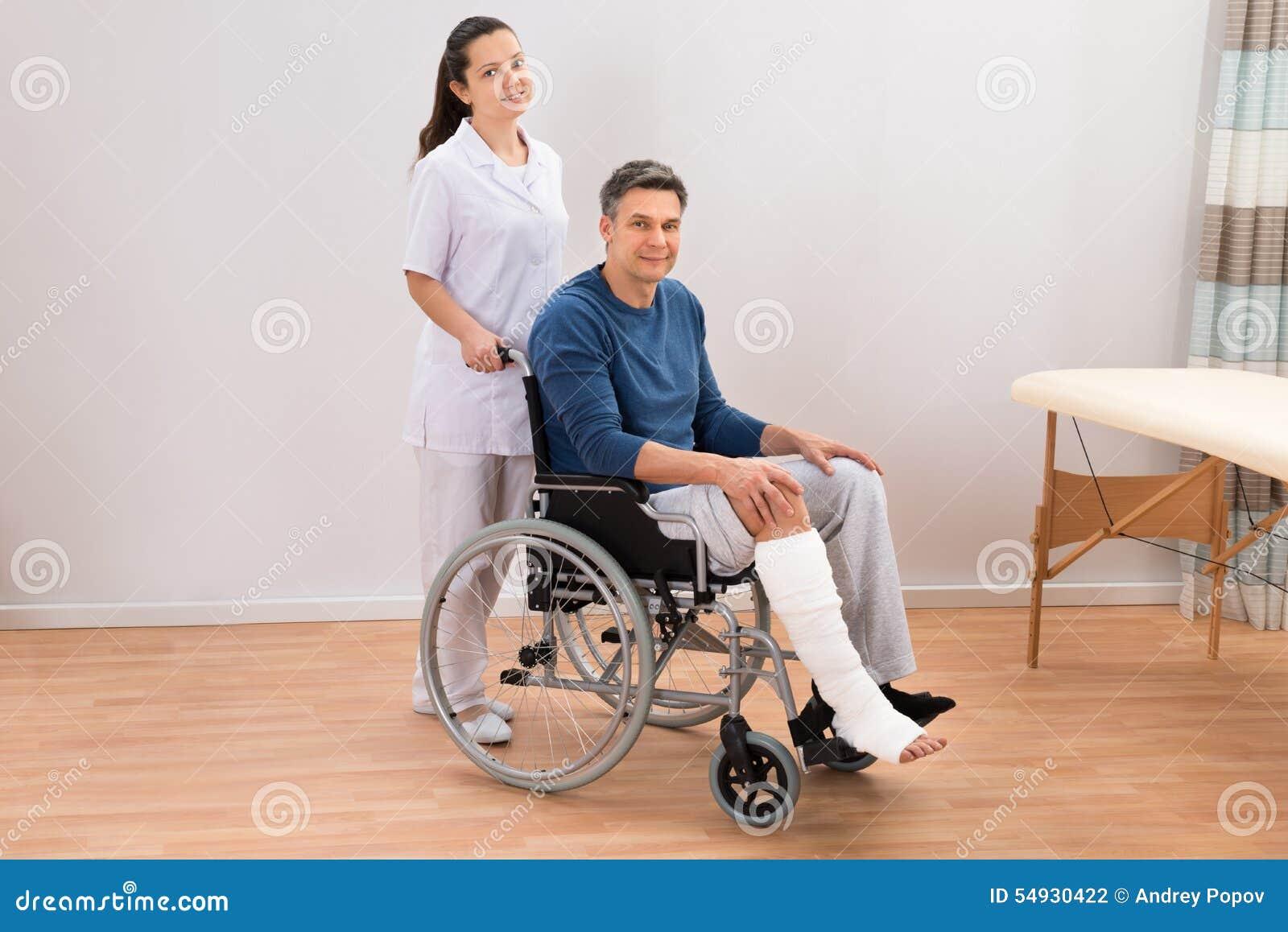 Medico con il paziente disabile sulla sedia a rotelle for Fisico sedia a rotelle