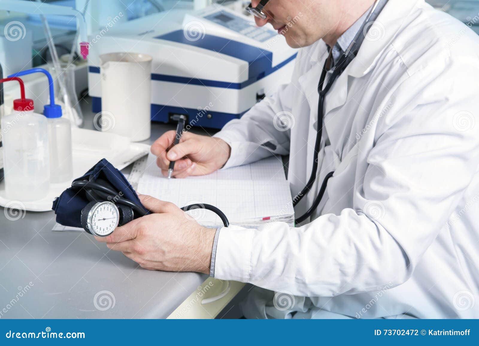 Medico con lo stetoscopio, i vetri e l abito scrivono sulla tavola