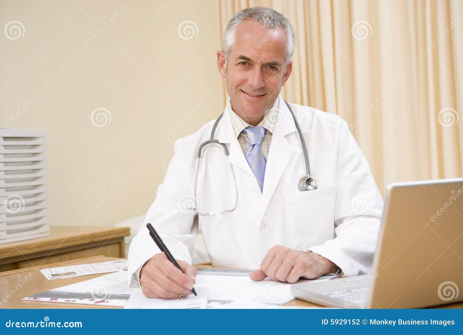 Medico con scrittura del computer portatile nell ufficio del medico