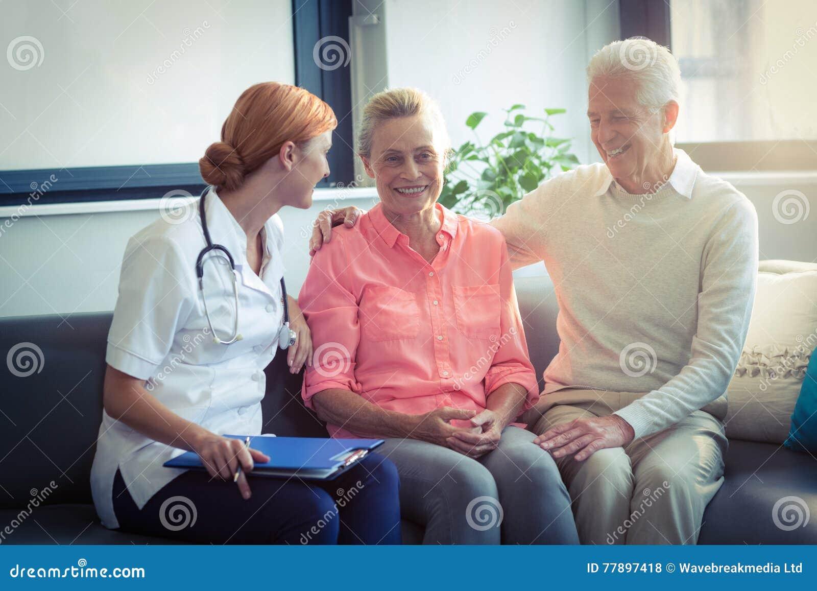 Medico e coppie senior che interagiscono a vicenda