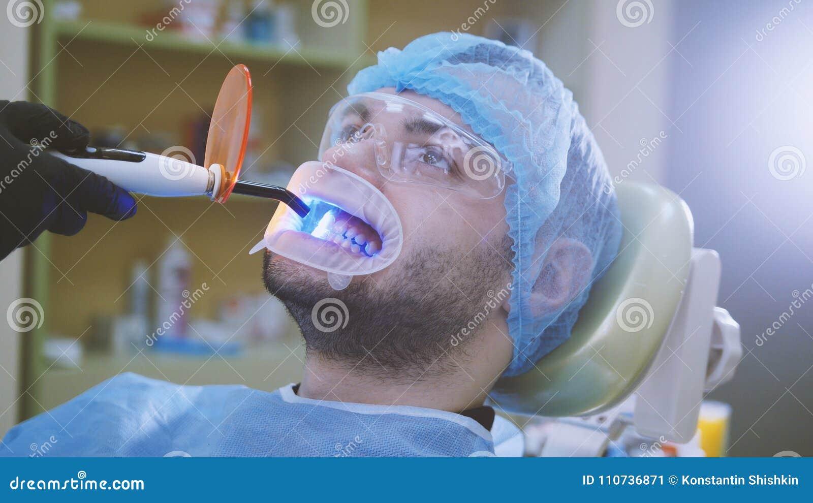 Medico e paziente con il retrattore nell ufficio dentario, pulendo con la luce ultravioletta e lo schermo protettivo arancio