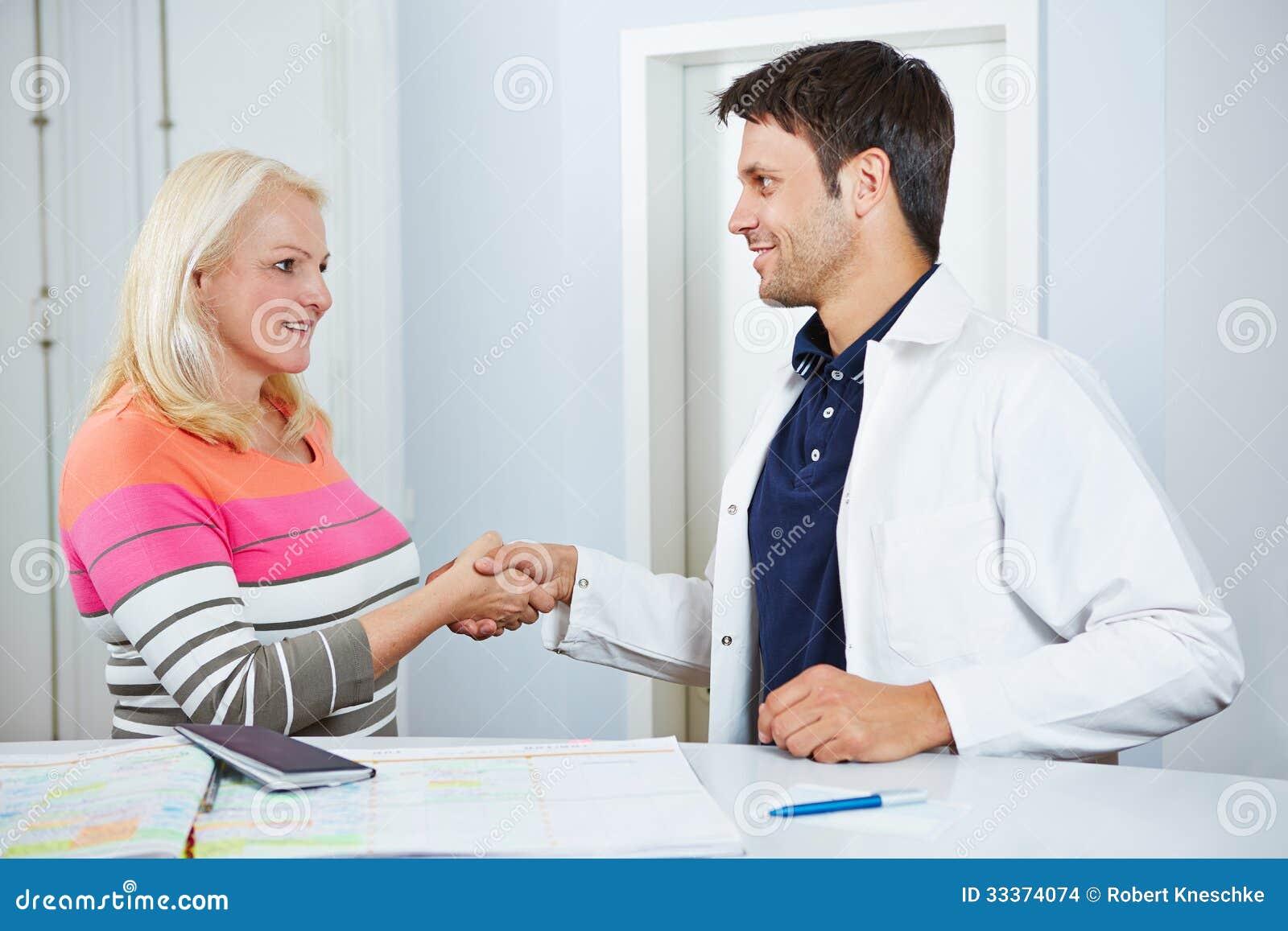Medico e paziente senior che stringono le mani