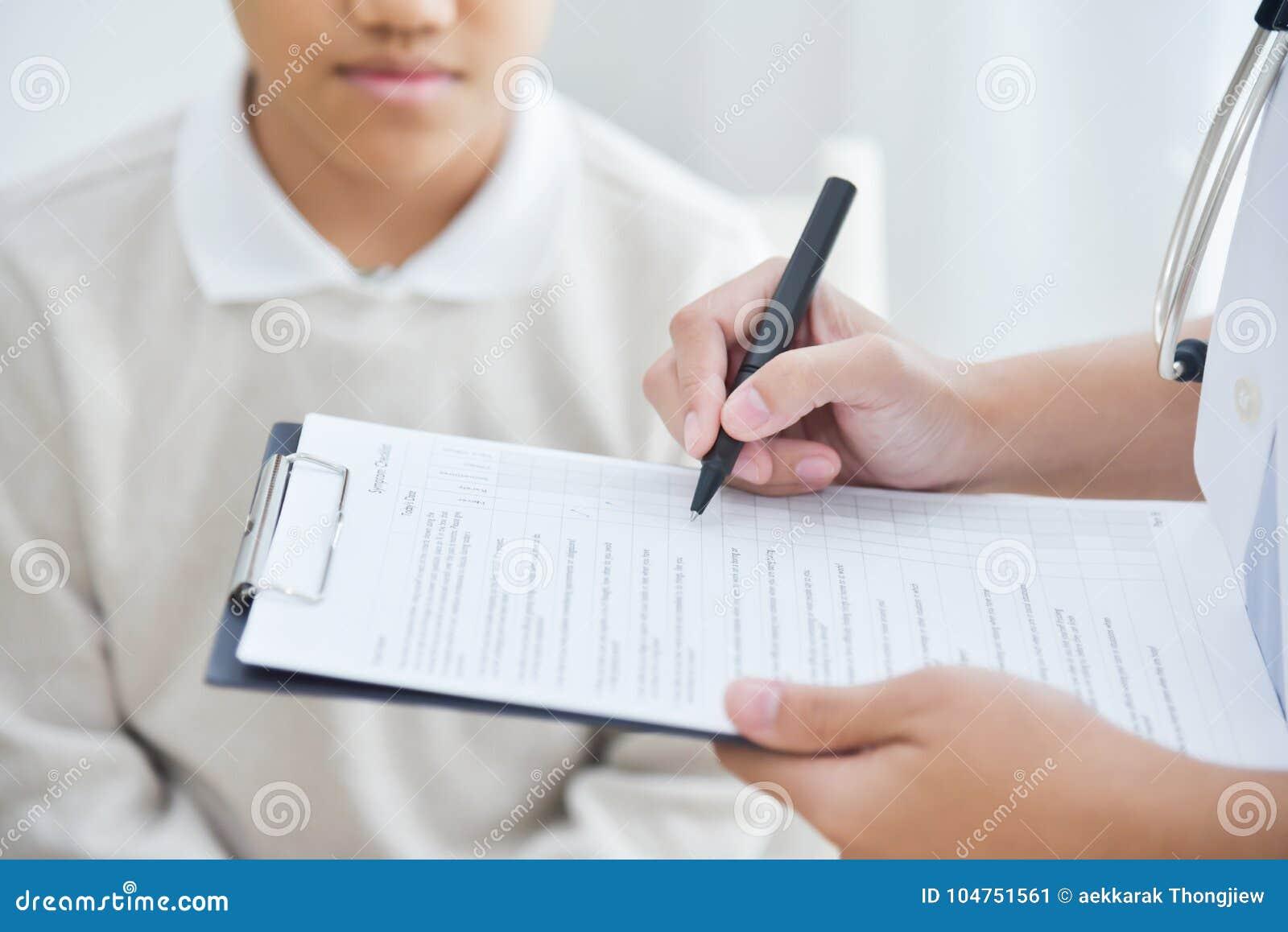 Medico femminile asiatico che prende nota sulla lista di controllo per un PA del ragazzino