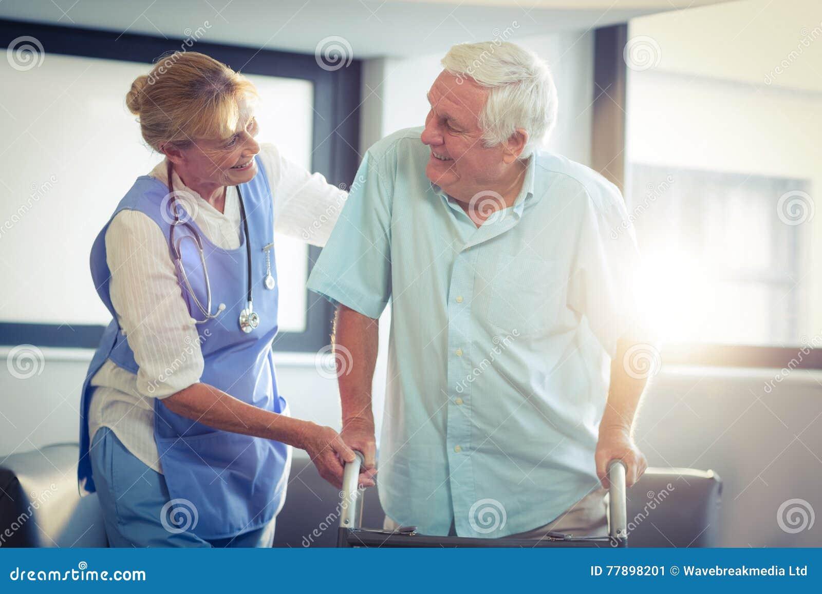Medico femminile che aiuta uomo senior a camminare con il camminatore