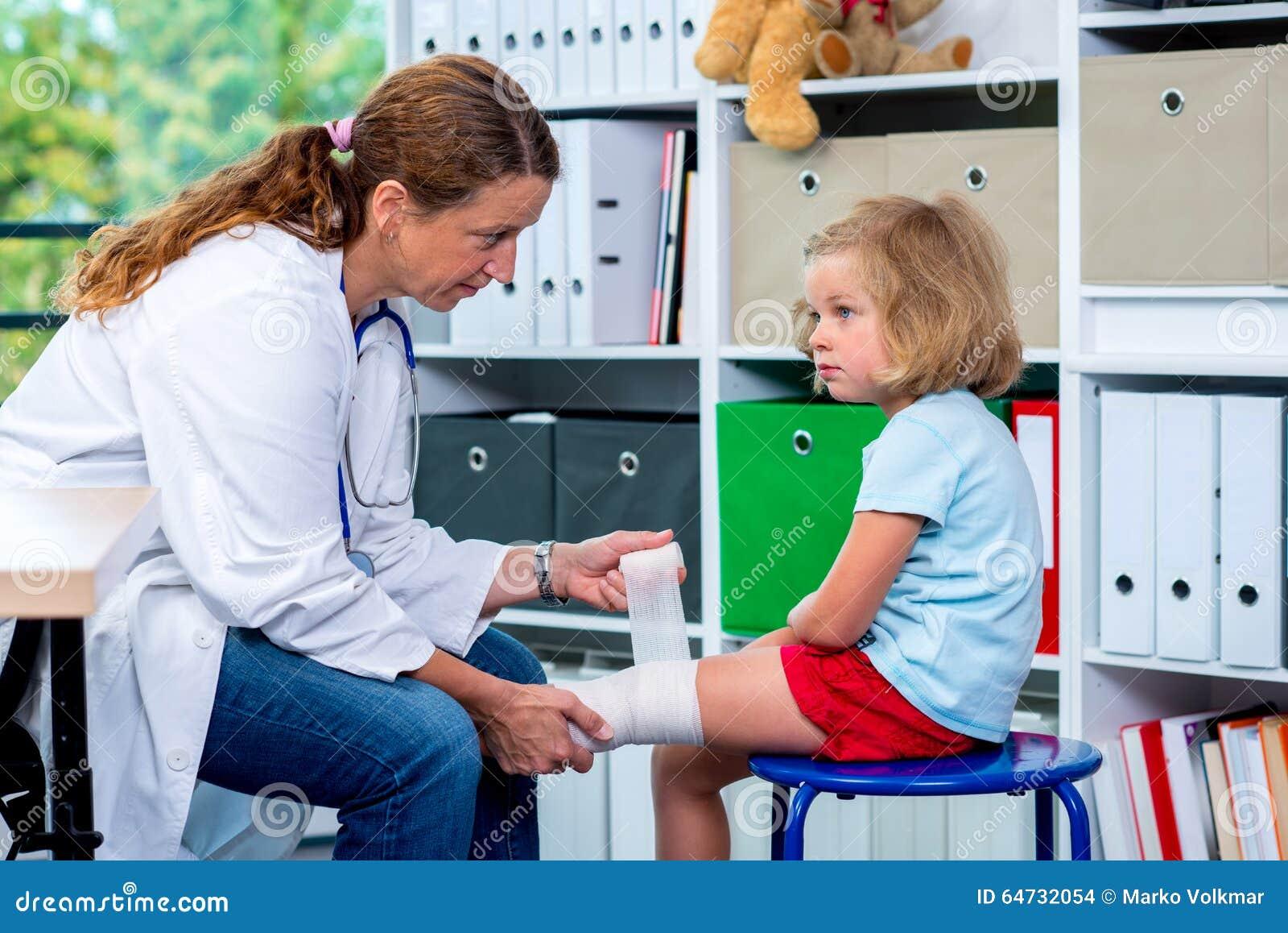 Medico femminile che benda la gamba dalla a della ragazza