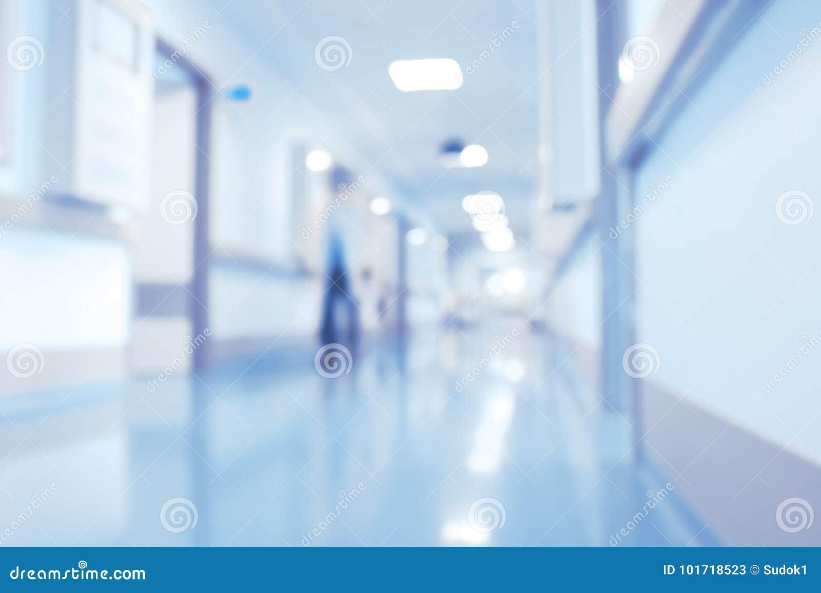 Medico maschio nell ingresso luminoso dell ospedale, parte posteriore unfocused