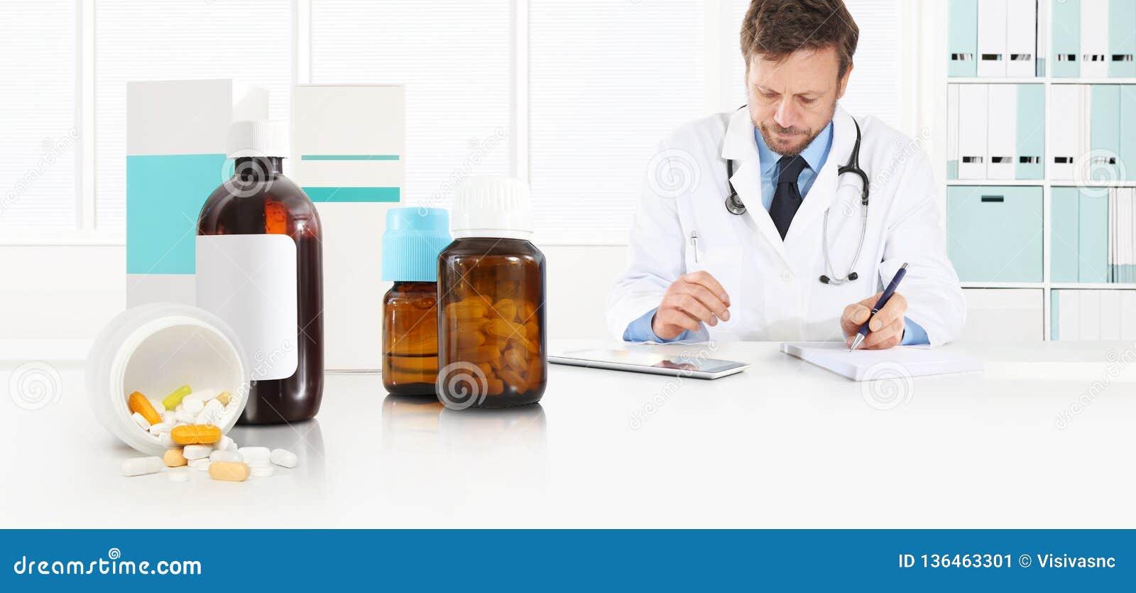 Medico prescrive la prescrizione che si siede all ufficio dello scrittorio con le pillole, i farmaci e le bottiglie della medicin