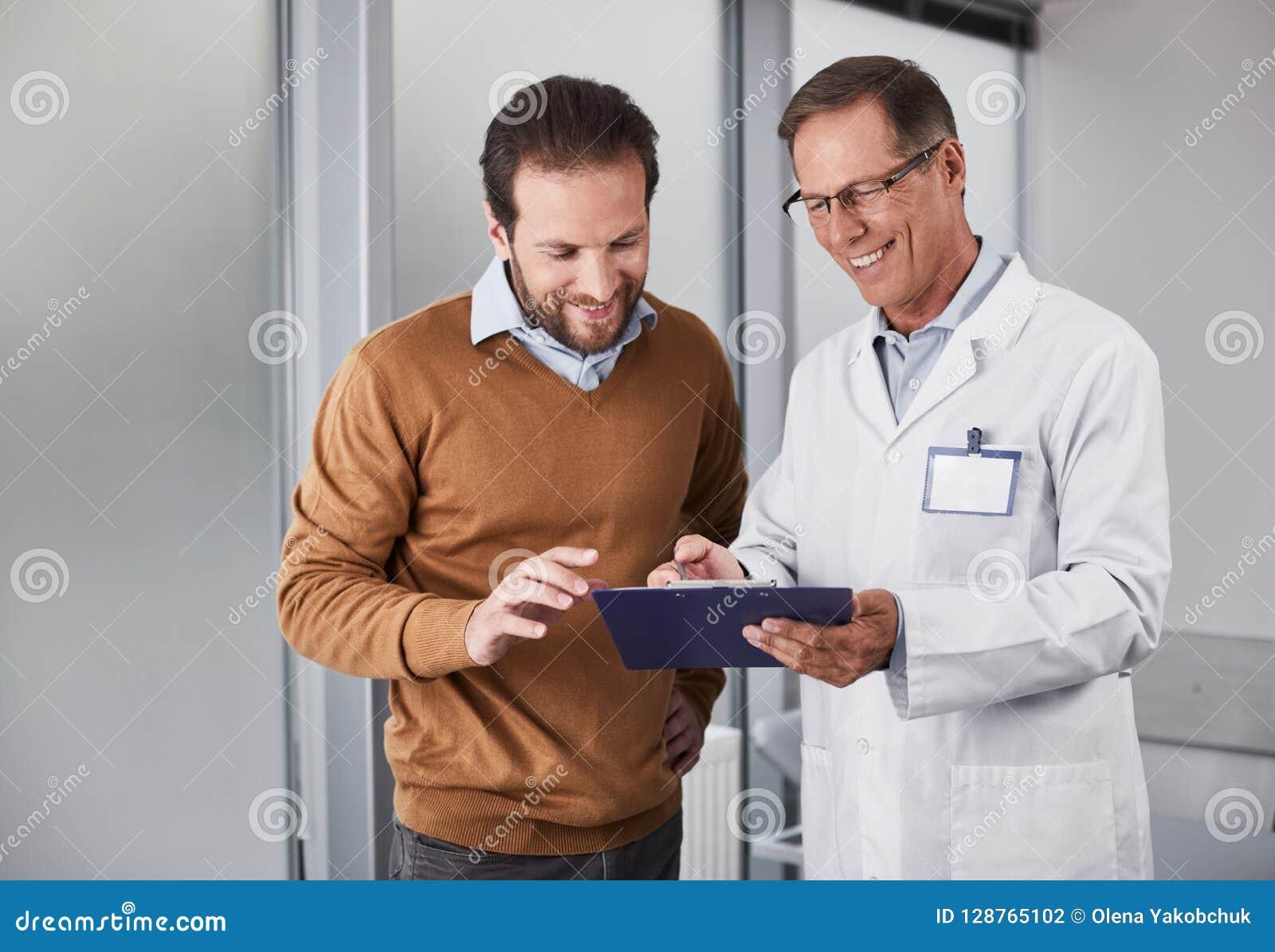 Medico sorridente che mostra i documenti dell uomo con le raccomandazioni