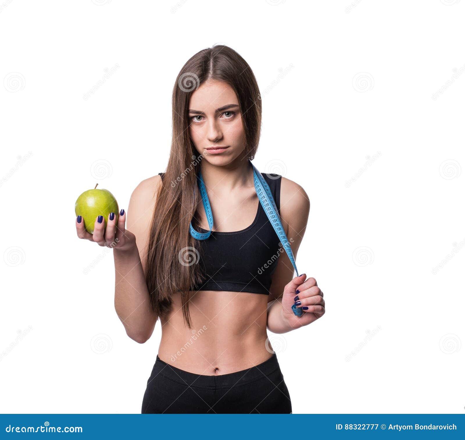 Medida magro e saudável da fita e a maçã da terra arrendada da jovem mulher isoladas no fundo branco Perda de peso e conceito da