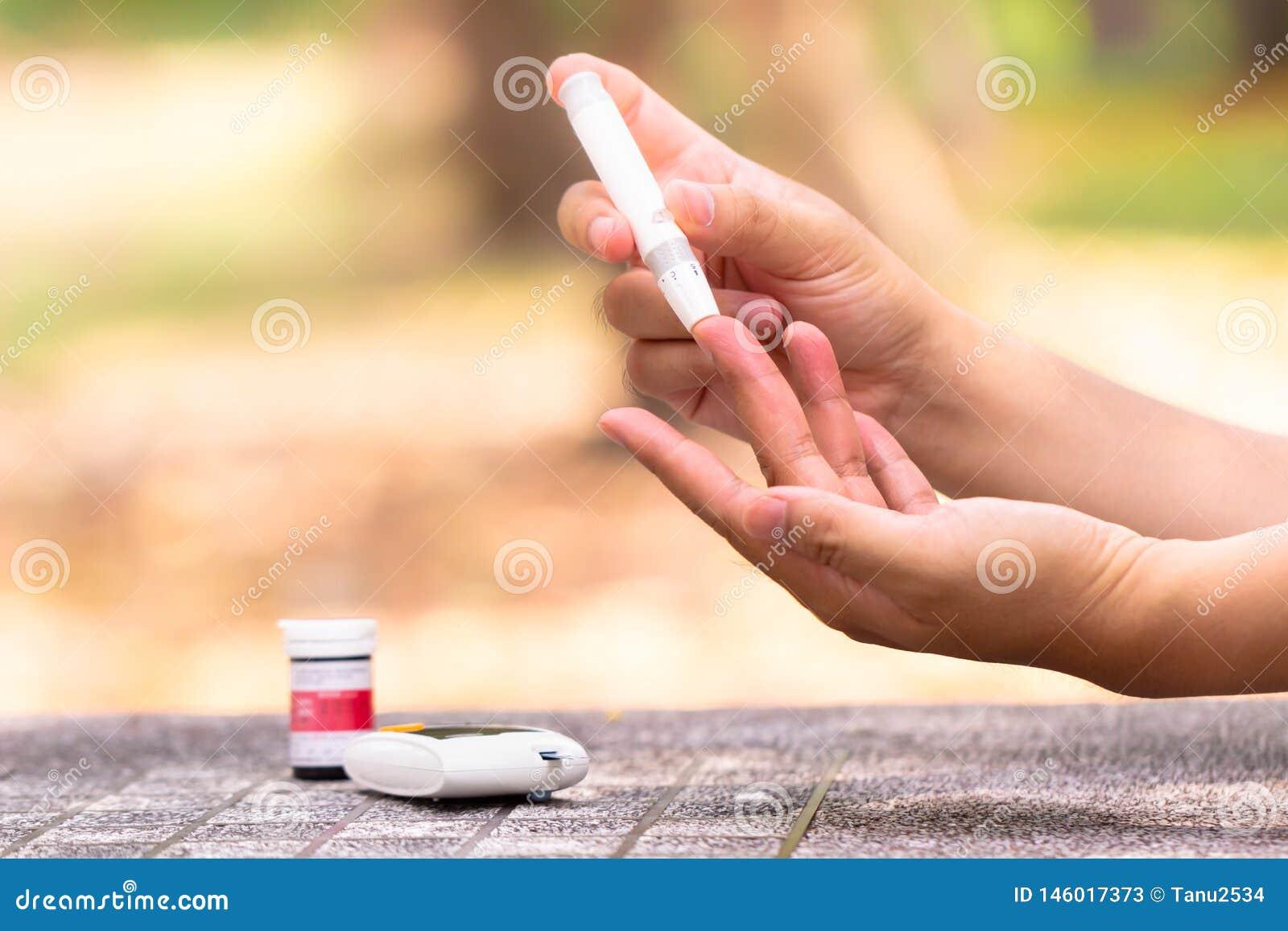 Medidor de glicose de sangue Feche acima das m?os da mulher usando a lanceta no dedo para verificar o n?vel do a??car no sangue p