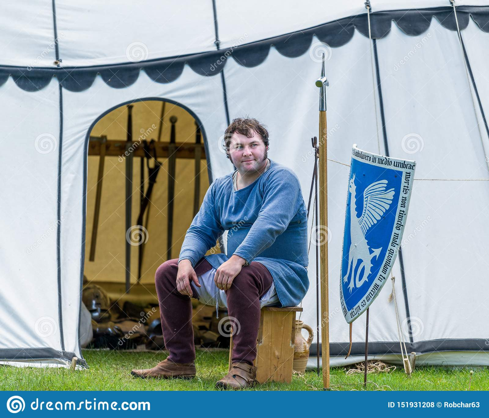 A medieval armorer sits outside his tent