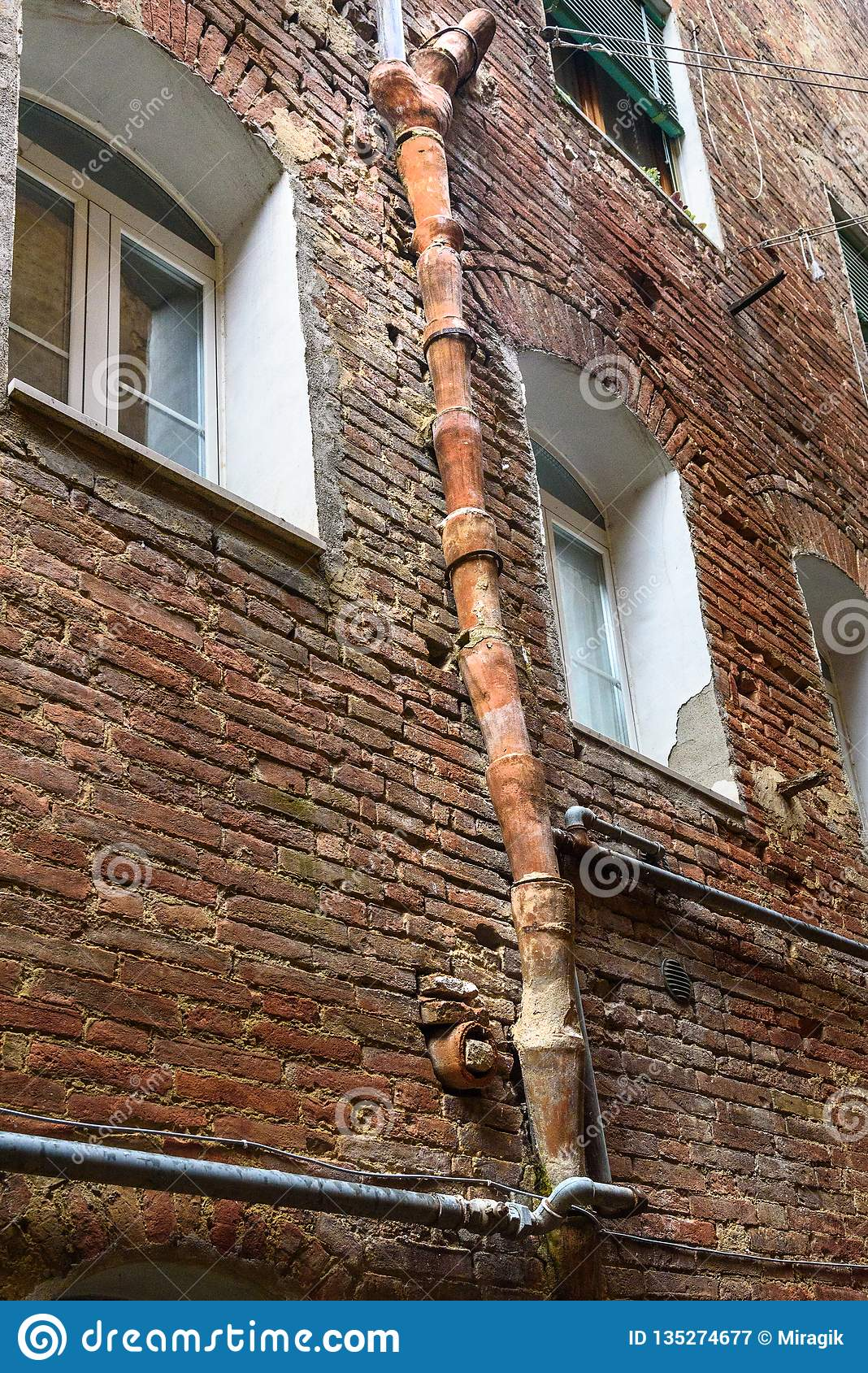 Medieval clay downspout on street Vicolo degli Orefici in Siena, Tuscany, Italy