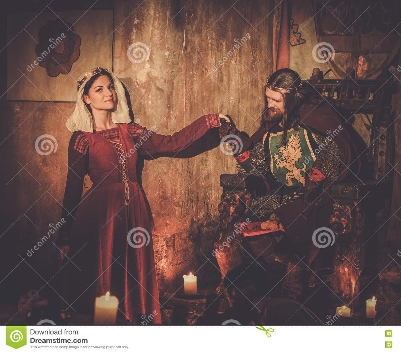 Medieval king with his queen in castle interior.