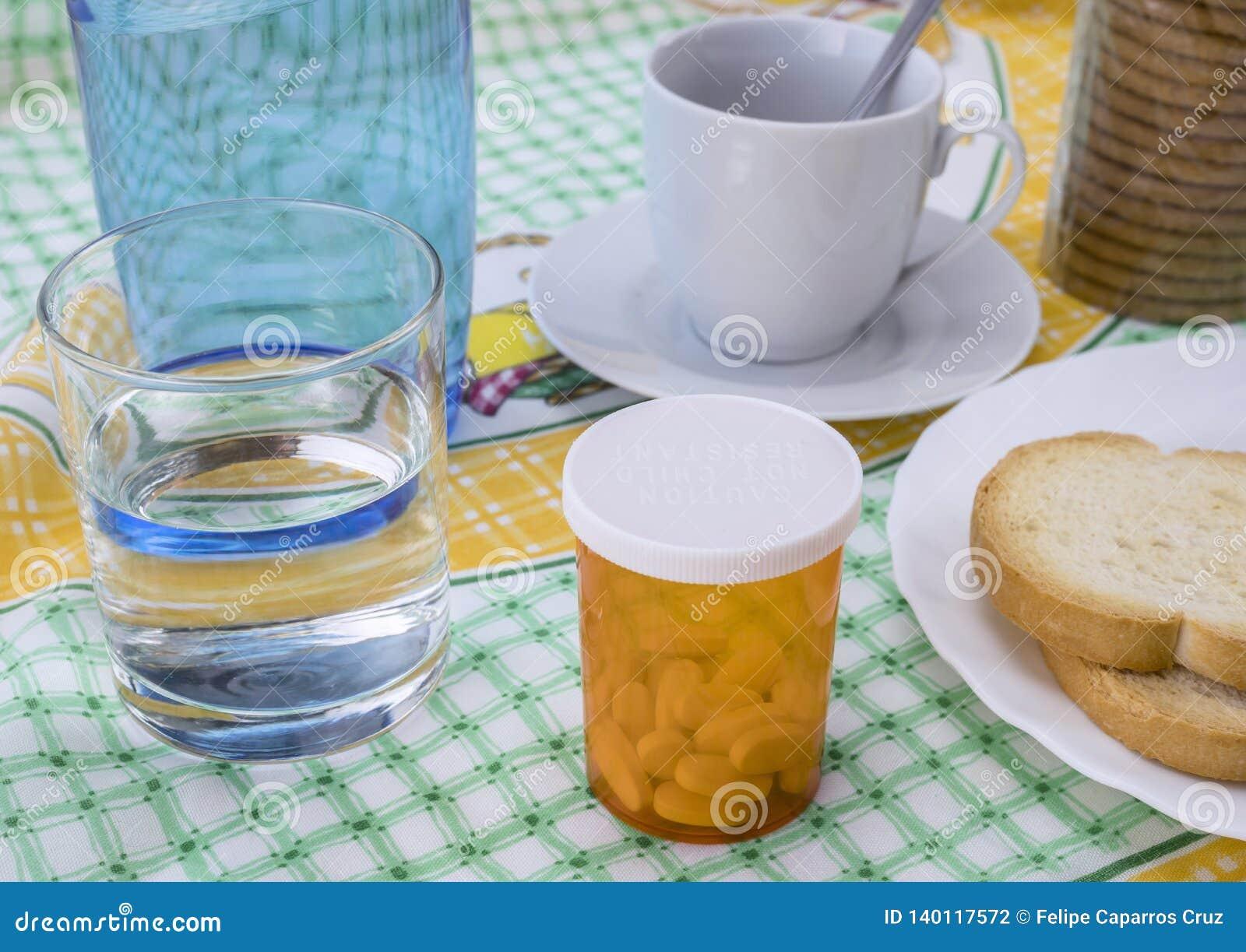 Medikation während des Frühstücks, Kapseln nahe bei einem Glas Wasser, Begriffsbild