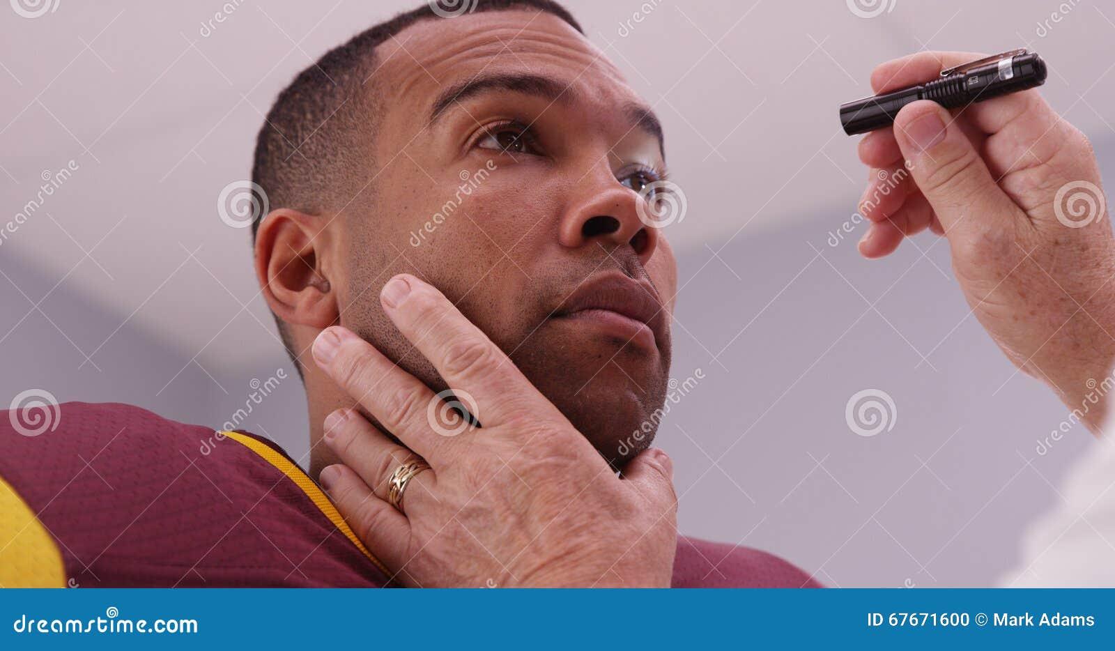 Medio oude arts die de ogen van de voetbalster met flitslicht controleren