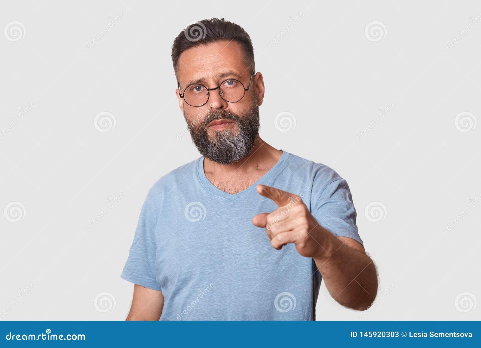 Medio retrato de la longitud del hombre envejecido medio atractivo con descubierto, señalando con el finger delantero en la cámar