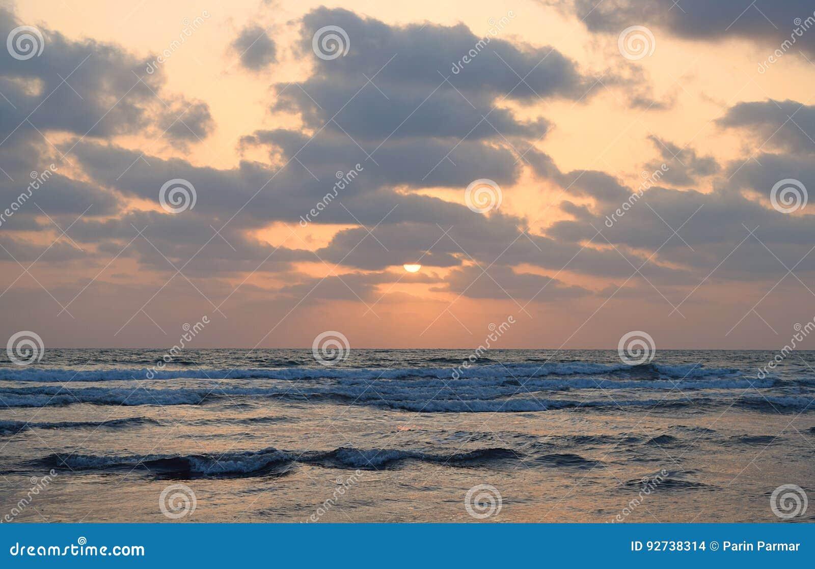 Medio Sun debajo de las nubes sobre el océano infinito - papel pintado natural de la puesta del sol