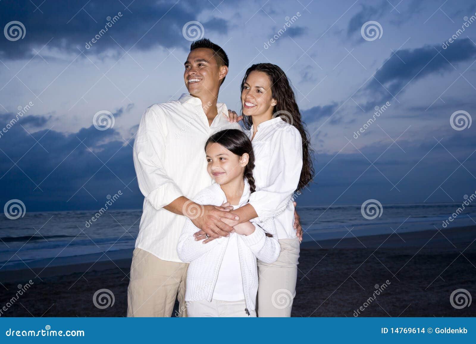 Medio-volwassen Spaanse familie die op strand bij dageraad glimlacht
