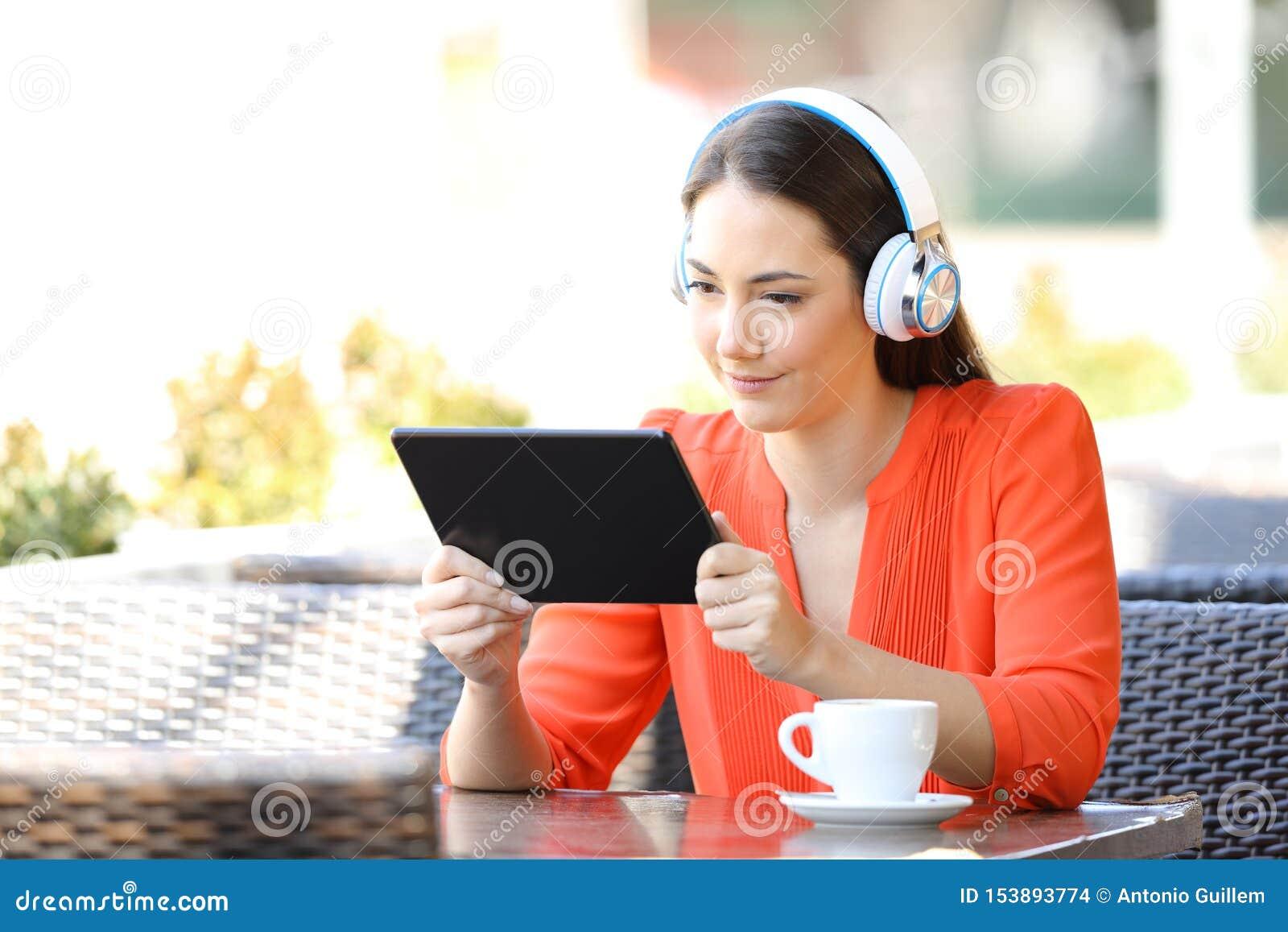 Medios de observación y que escuchan de la mujer en una tableta en una barra