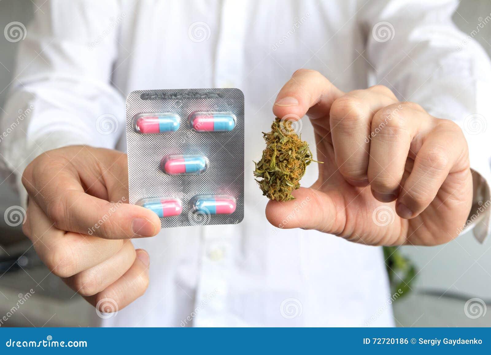 Medique a mão que guarda o botão do cannabis e de comprimidos médicos