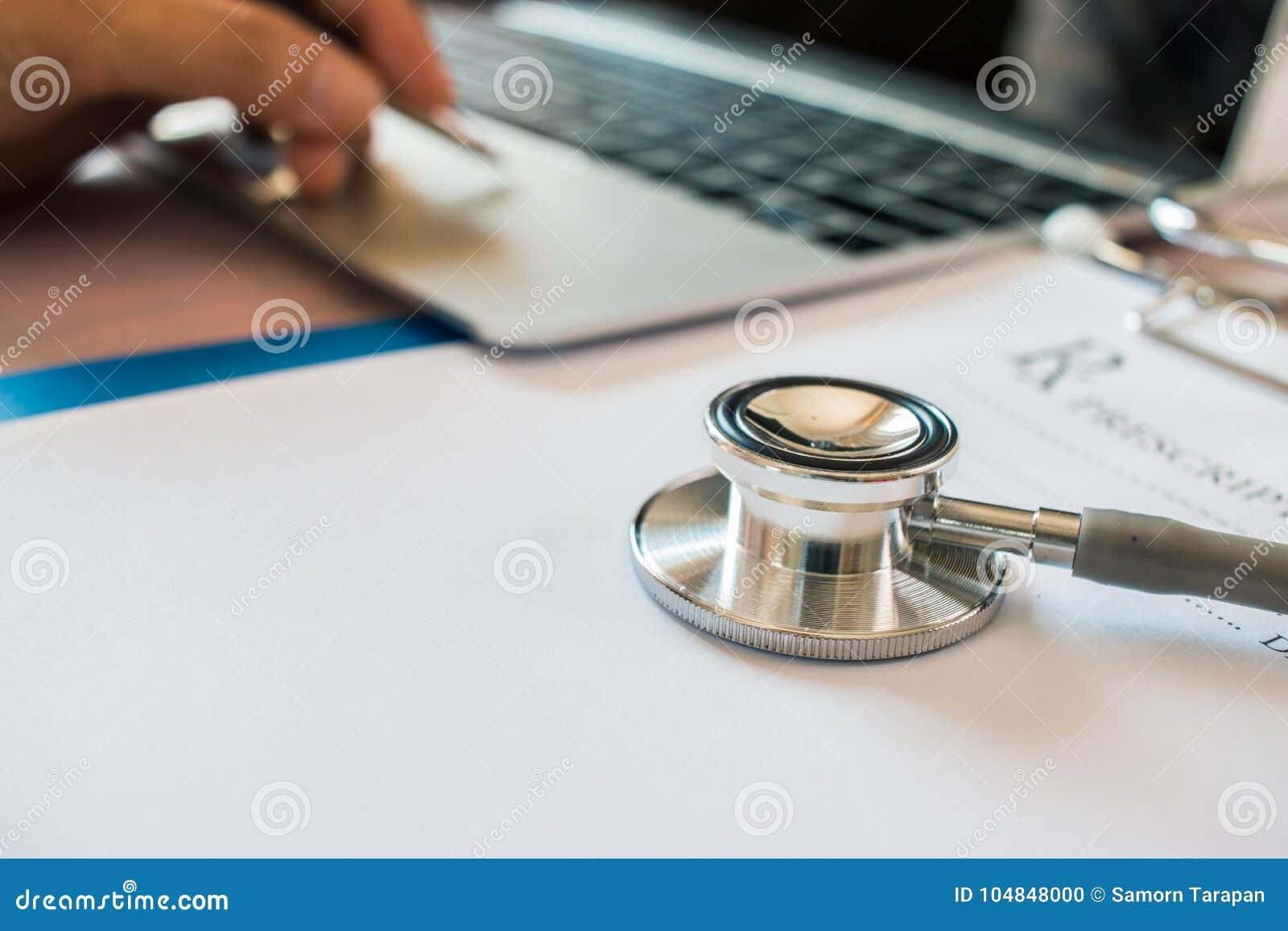 Medique o ` s que trabalha no laptop, escrevendo a prancheta da prescrição com os dobradores do papel de informação do registro n