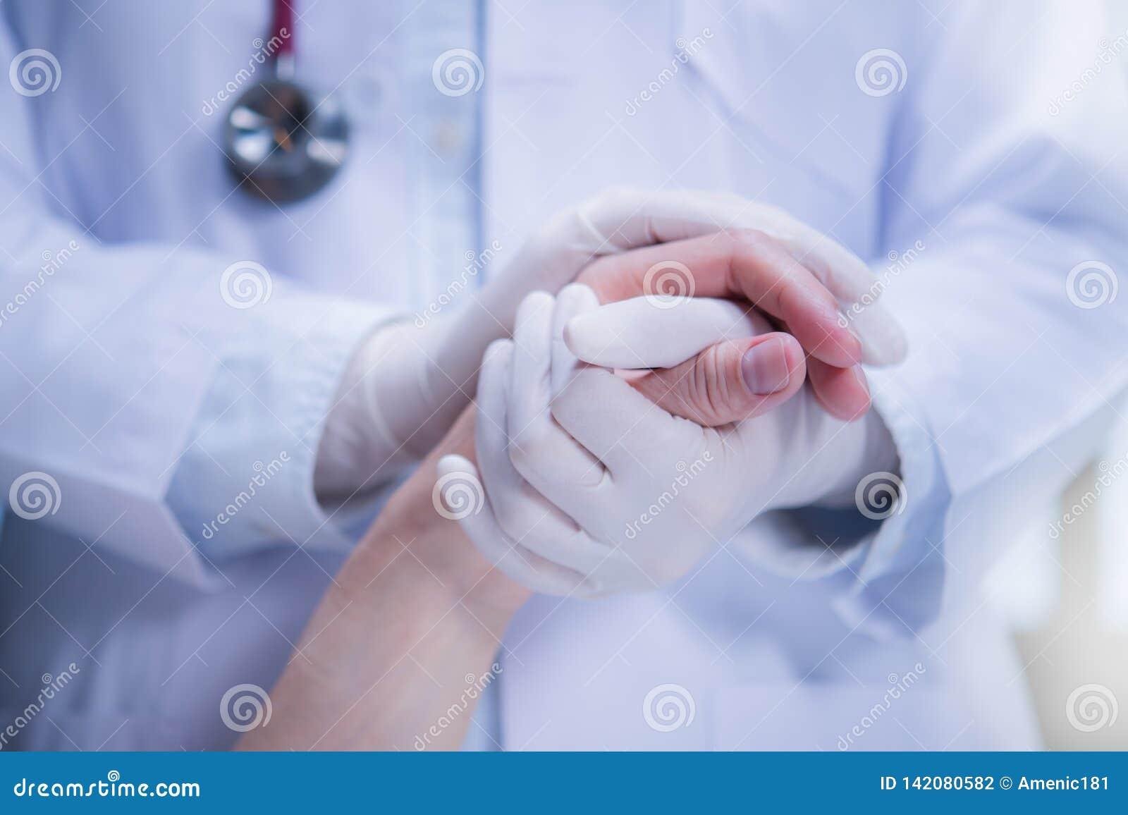 Medische arts die latexhandschoenen dragen die patient's hand houden om steun te geven in het ziekenhuis het plaatsen