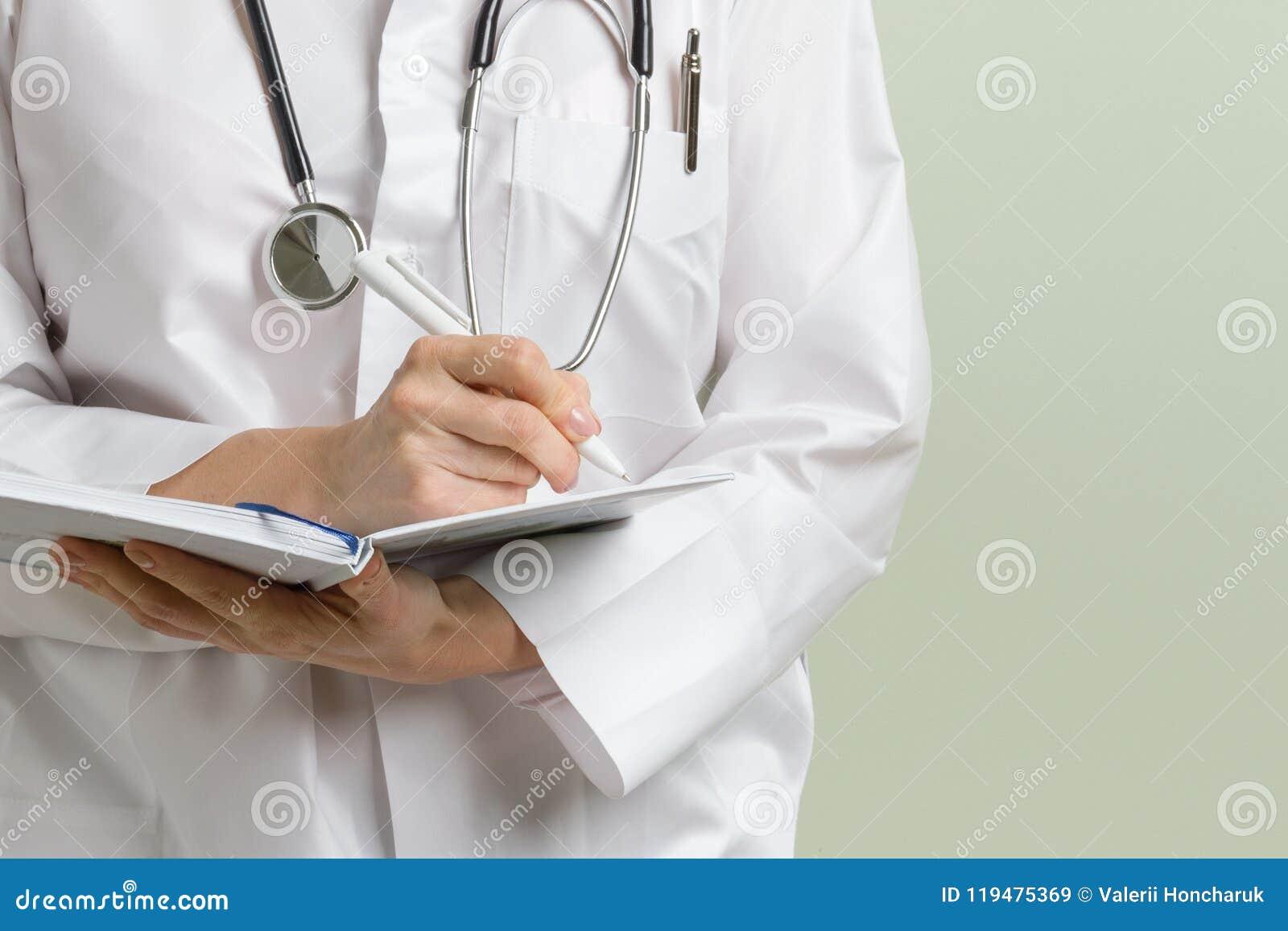 Medische artsenvrouw met stethoscoop die nota s over haar blocnote nemen tegen groene achtergrond De ruimte van het exemplaar