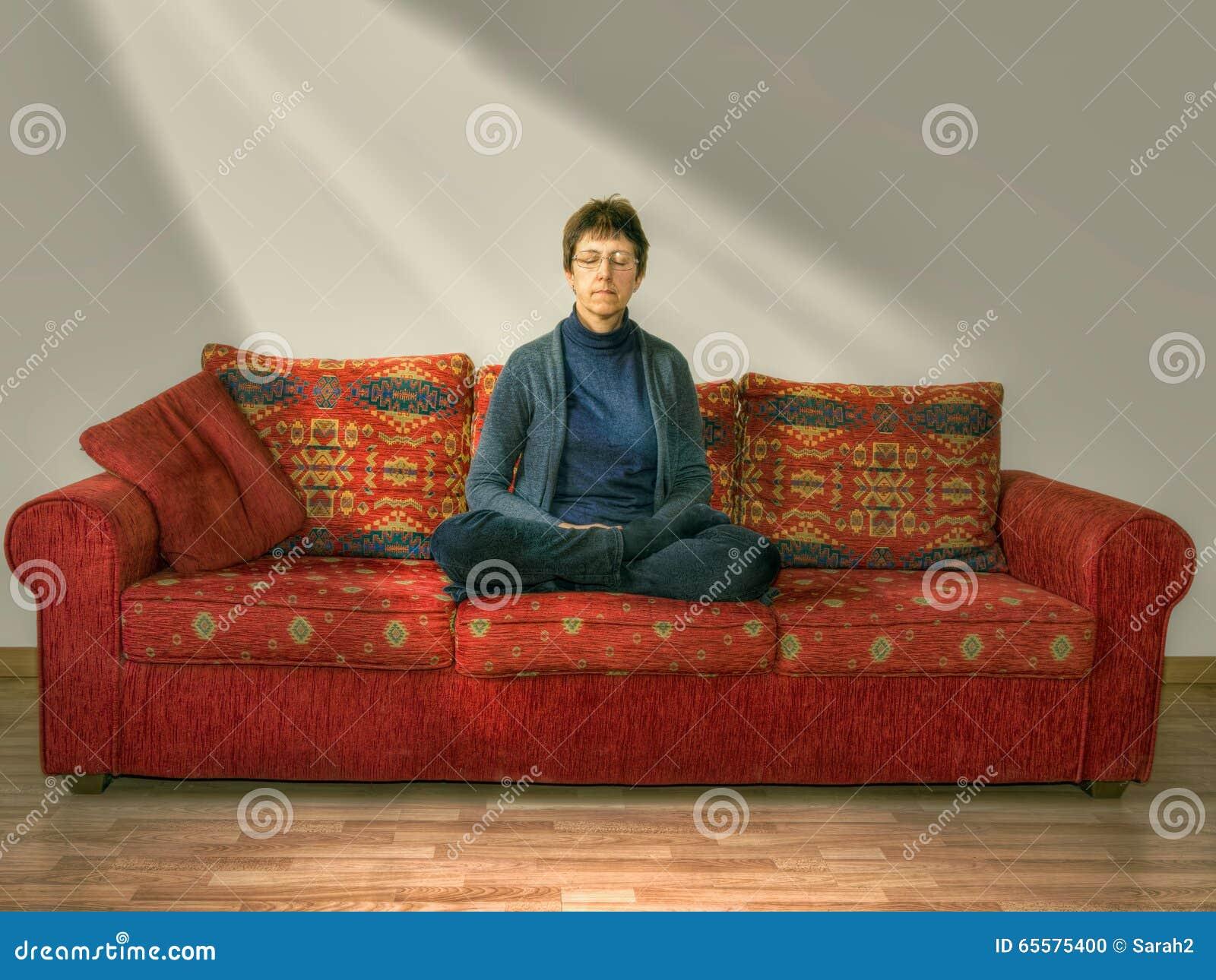 Meditação, abrandamento Mulher madura, mais idosa em casa no sofá, grupo