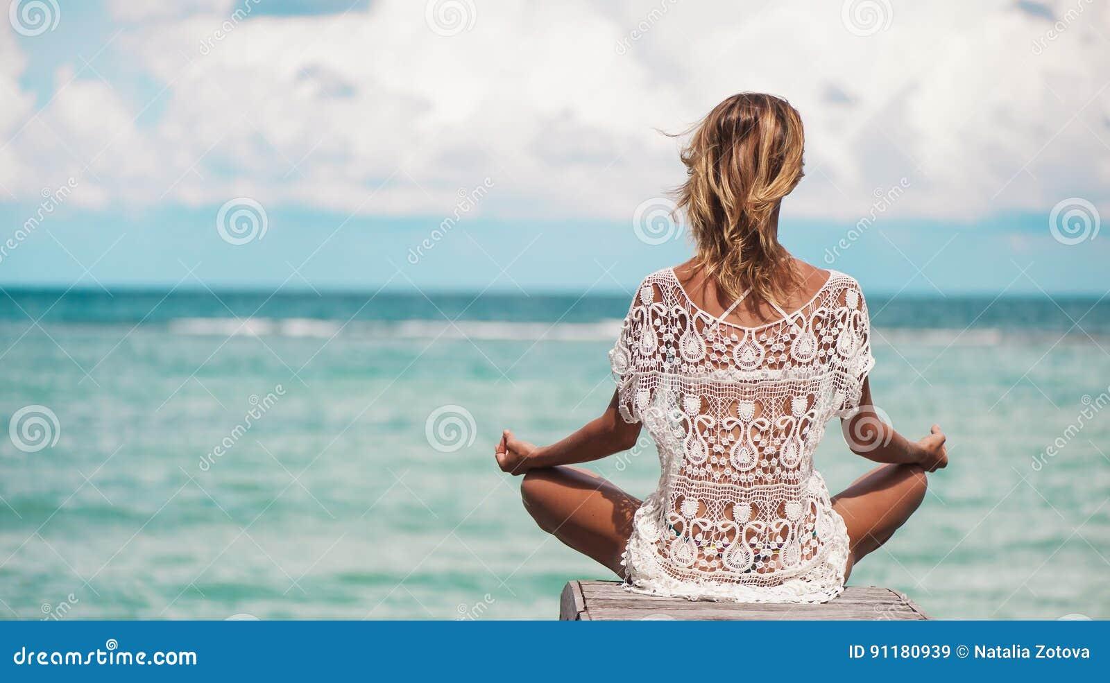 Meditação da mulher em uma pose da ioga na praia