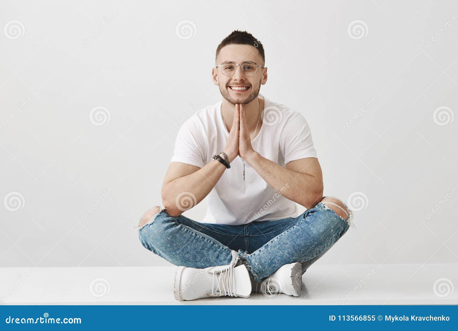 Meditação e conceito das emoções Homem novo à moda atrativo com a barba, os vidros vestindo e o equipamento na moda, sentando-se