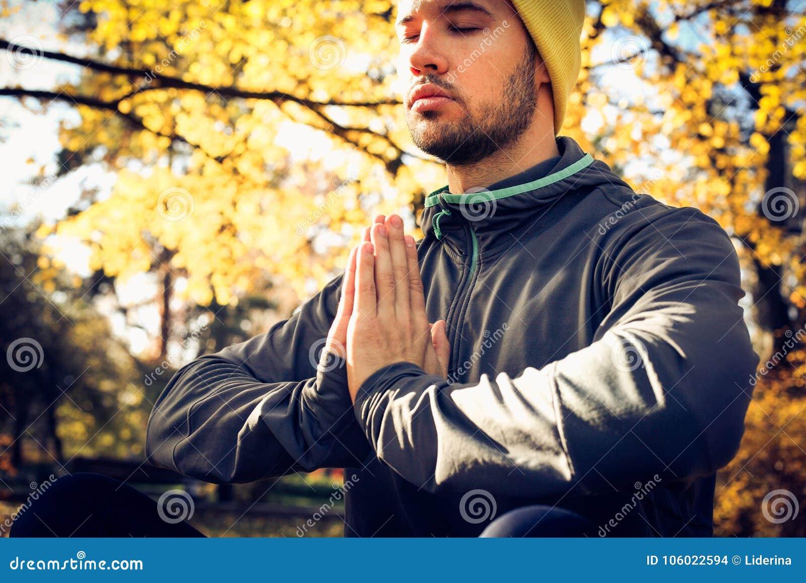 Meditación del hombre joven en naturaleza Ojos cerrados