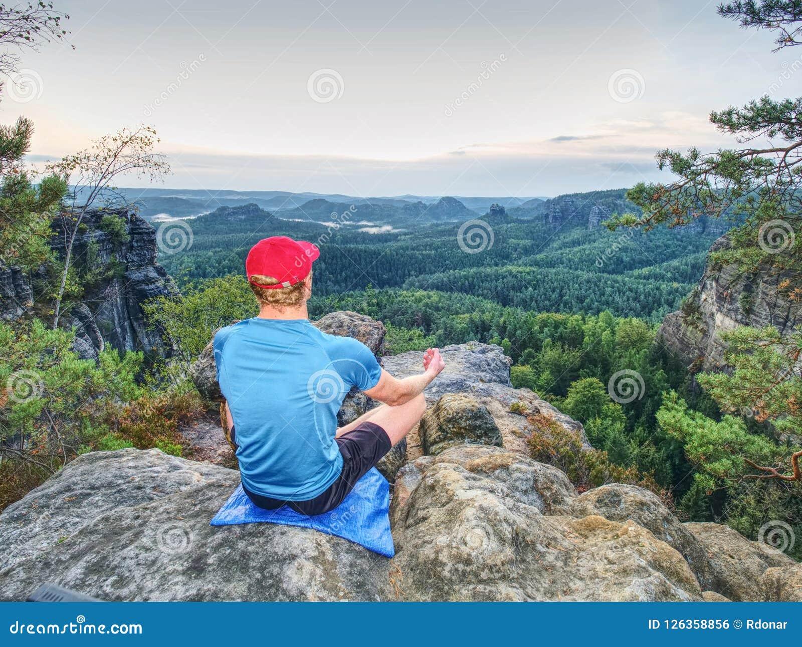 Meditando a posição da ioga sobre a parte superior do montanhas O homem meditate