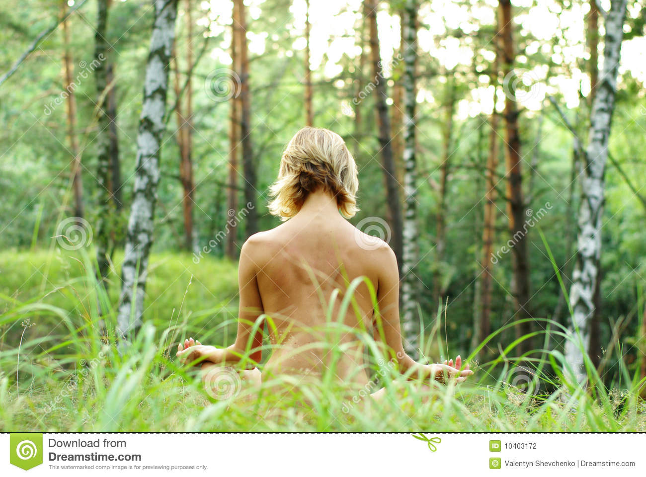 Beautiful woman doing meditation in forest on a sunny day