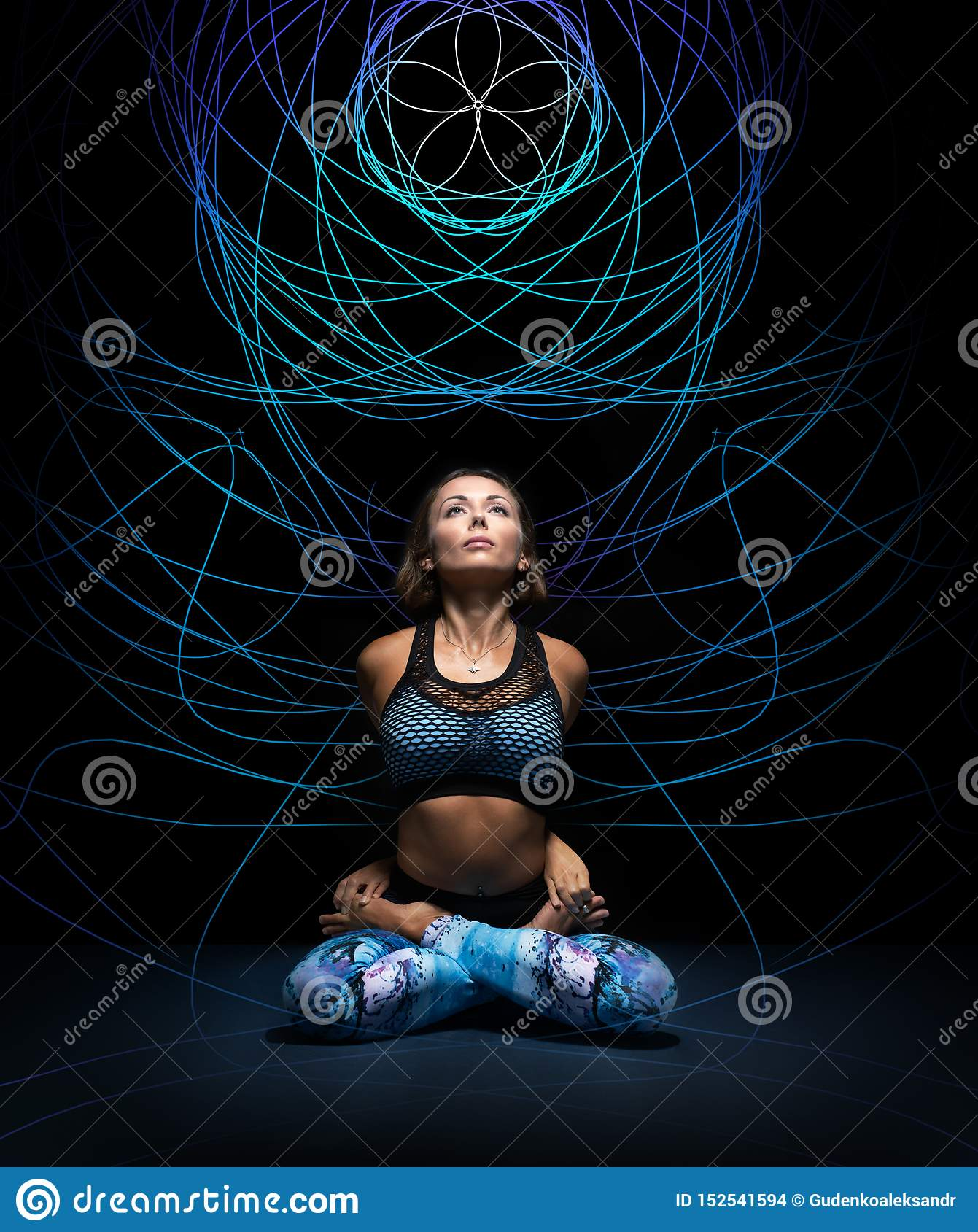 Beautiful young woman in padmasana pose. Colorful mandala on black background behind