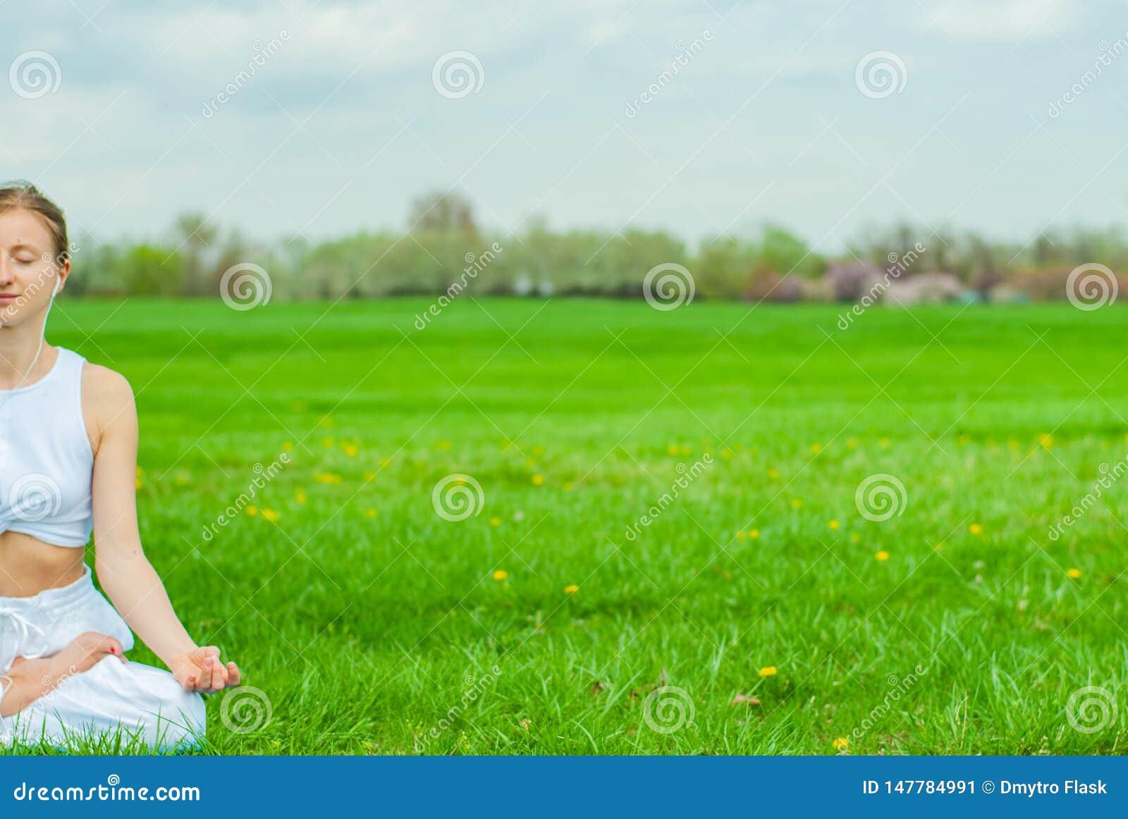 Meditation Mulher que faz a ioga e que escuta para relaxar a m?sica