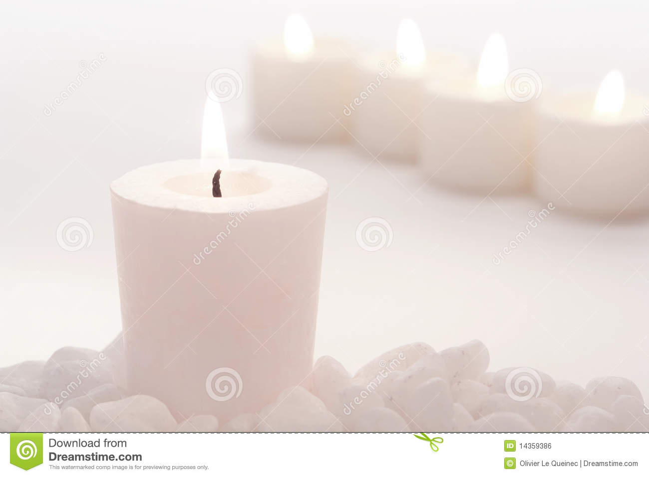 White votive candle burning softly with row of lit pale candles for