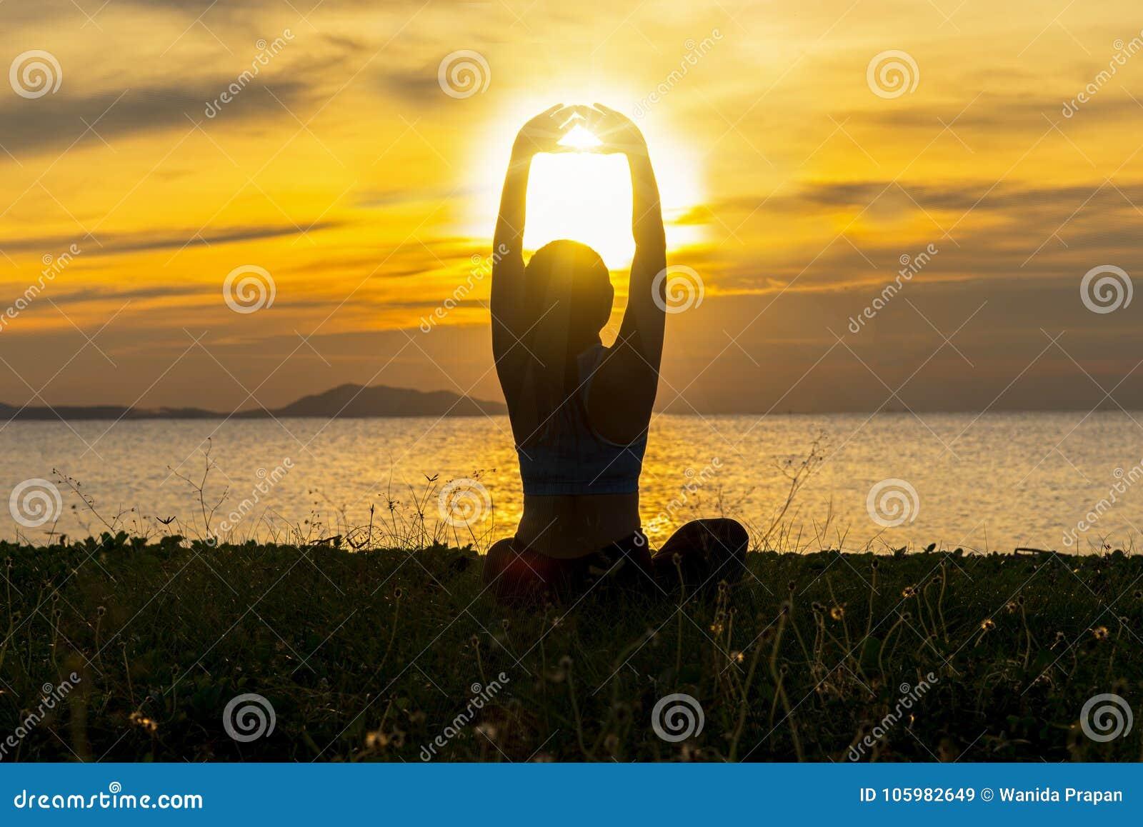 Meditationsyogalebensstil-Frauenschattenbild auf dem Seesonnenuntergang, entspannen sich wesentliches