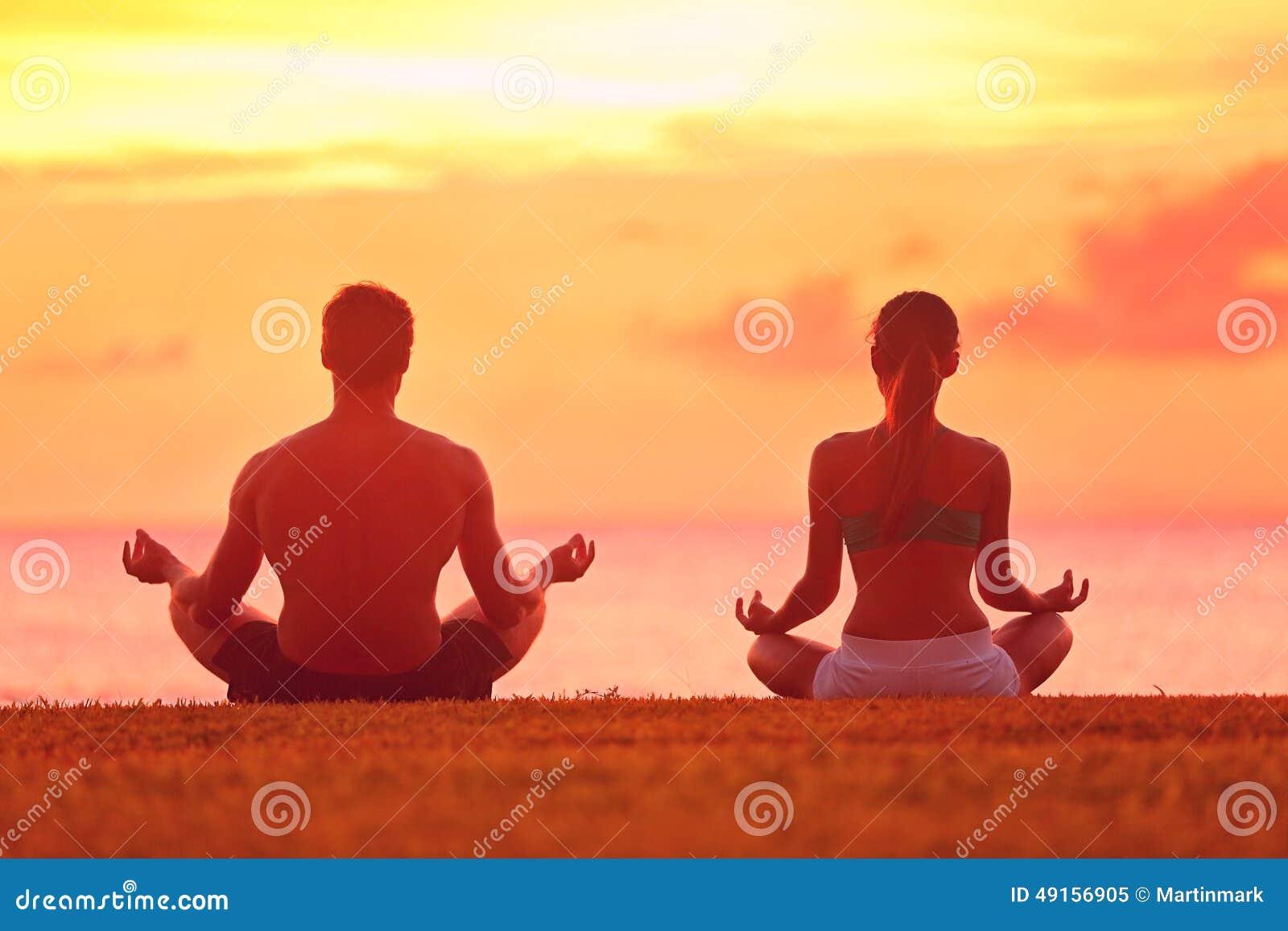 Meditationsyogapaare, die bei Strandsonnenuntergang meditieren